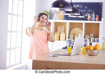 álló, nő, laptop, fejhallgató, fiatal, jókedvű, időz, számítógép, zene hallgat, portré, használ, konyha