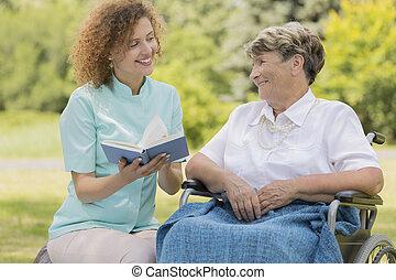 ápoló, felolvasás, öregedő woman, alatt, egy, kert