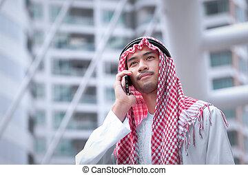 árabe, hombre de negocios, utilizar, teléfono celular, y, negocio moderno, ciudad, plano de fondo
