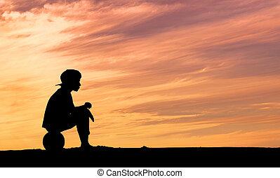 árnykép, közül, egy, fiú ül, képben látható, labdarúgás, vagy, focilabda, tengerpart, noha, napnyugta, háttér