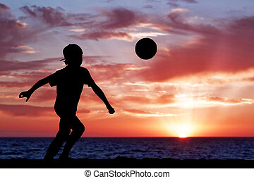 árnykép, közül, egy, fiú játék foci, vagy, futball, tengerpart, noha, gyönyörű, napnyugta, háttér