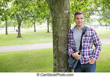 árvore, olhar, câmera, estudante, inclinar-se, sorrindo