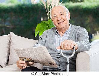 äldre bemanna, med, tidning, och, käpp, sitta på soffa