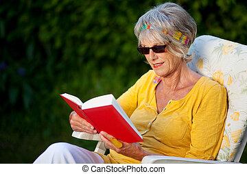 äldre, dam, läsning en boka, med, solglasögon