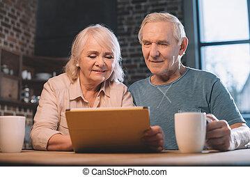 äldre koppla, användande, digital tablet, hemma
