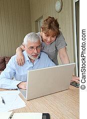 äldre koppla, användande laptop, dator, hemma