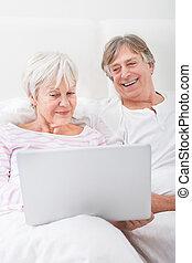 äldre koppla, blomsterbädd, tittande vid, laptop