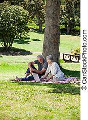 äldre koppla, ha picknick, i trädgården