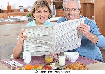 äldre koppla, läsande tidning