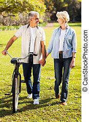 äldre koppla, vandrande, a, cykel, i park, gårdsbruksenheten räcker
