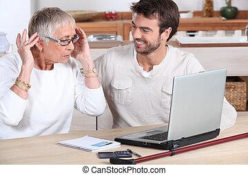 äldre kvinna, användande dator