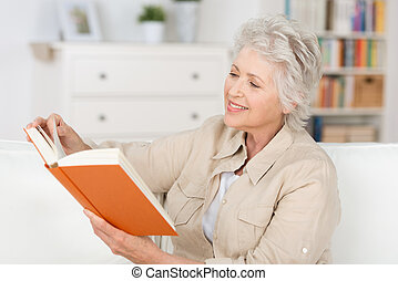 äldre kvinna, avslappa hemma, läsning en boka