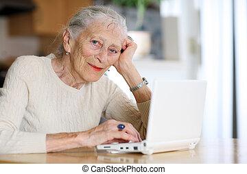 äldre kvinna, maskinskrivning, med, dator, hemma