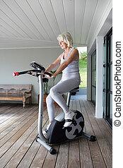 äldre kvinna, på, en, övning maskin