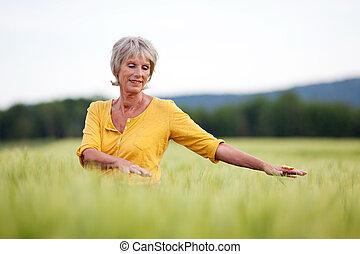 äldre kvinna, vandrande, fastän, fält