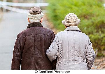äldre par promenera, i parken