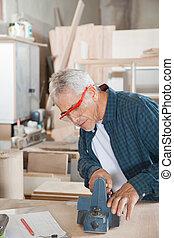 älter, zimmermann, gebrauchend, elektrisch, planer, in, werkstatt