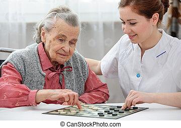 ältere frau, damespiel, spielende