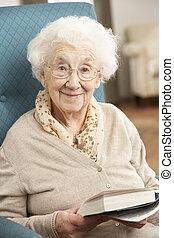 ältere frau, entspannend, stuhl, hause, lesend buch