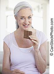 ältere frau, essen schokolade
