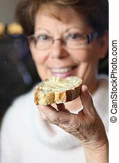 ältere frau, essende, a, scheibe toasts