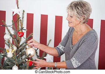 ältere frau, hängender , weihnachtsdekorationen