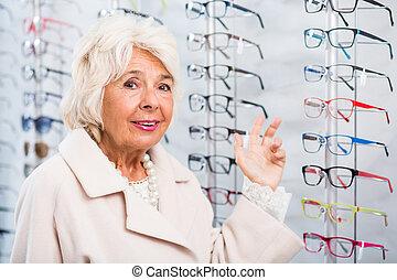 ältere frau, in, optiker, kaufmannsladen