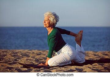 ältere frau, joga, wasserlandschaft
