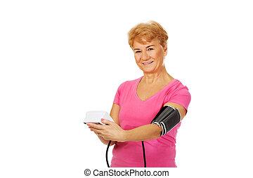 ältere frau, messender blutdruck, mit, automatisch, manometer