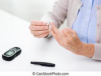 ältere frau, mit, glucometer, prüfung, blut, zucker