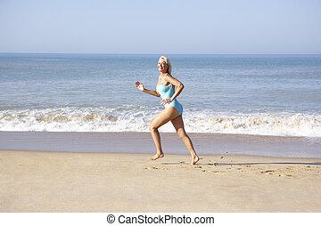 ältere frau, sandstrand, rennender