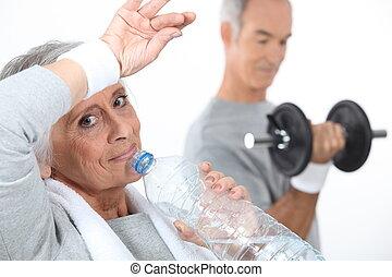 ältere frau, trinkwasser, nach, turnhalle, sitzung