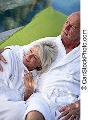ältere paare, bademäntel, faulenzend
