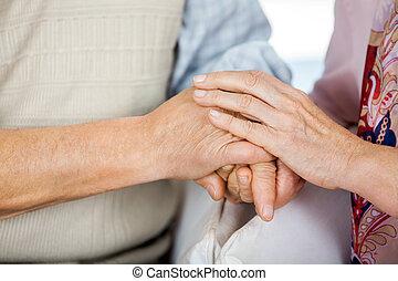 ältere paare, halten hände, während, sitzen stühlen