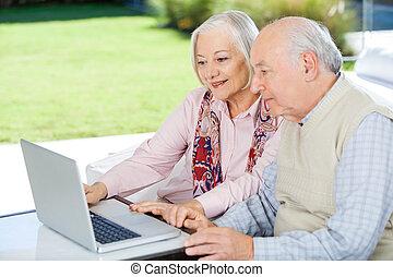 ältere paare, laptop benutzend