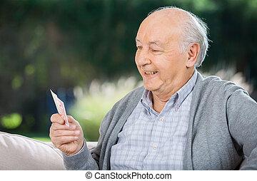 älterer mann, anschauen, karten, während, sitzen couch