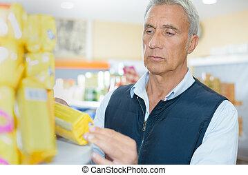 älterer mann, anschauen, paket, von, kekse, in, kaufmannsladen