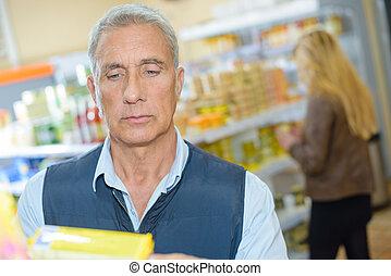älterer mann, anschauen, produkt, in, kaufmannsladen