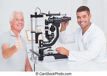 älterer mann, ausstellung, daumen hoch, während, sitzen, mit, optiker