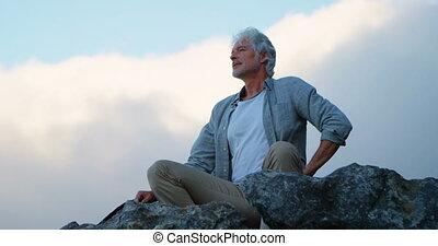 älterer mann, entspannend, auf, a, gestein, an, landschaft,...