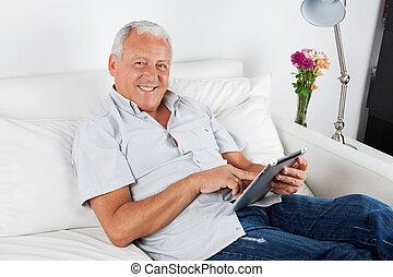 älterer mann, gebrauchend, digital tablette, pc