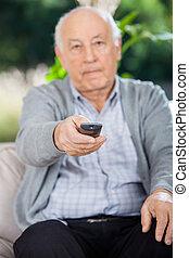 älterer mann, gebrauchend, fernsteuerung, während, sitzen couch