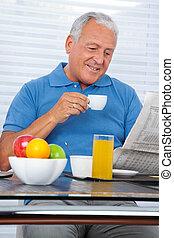 älterer mann, lesend zeitung