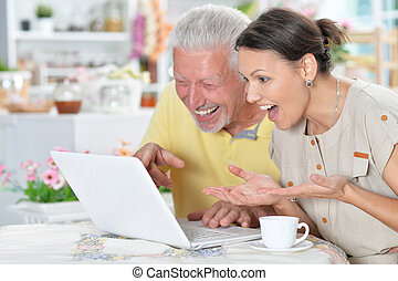 älterer mann, mit, junge frau, laptop benutzend