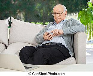 älterer mann, textmessaging, durch, smartphone, an, vorhalle