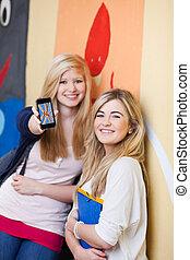 école, concept, femme, unité, étudiant, portrait, heureux, afficher, ami, mobilephone