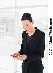 élégant, mobile, femme affaires, choqué, regarder, téléphone