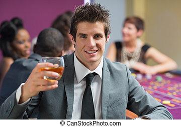 élevant verre, homme, whisky, table, roulette