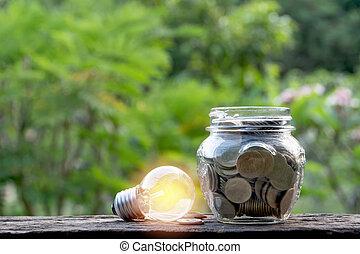 énergie, économie, ampoule, et, pièces, dans, pot verre, sur, nature, arrière-plan., économie, comptabilité, et, financier, concept.