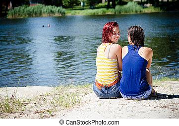 été, adolescent, partage, &, temps, filles, deux, regarder, appareil photo, arrière-plan vert, dehors, sourire, joyeux, heureux